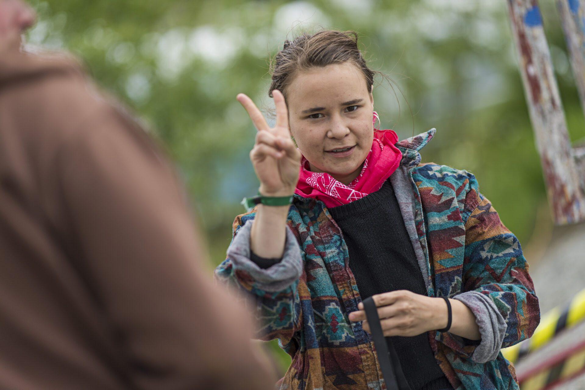 Jente som gjør peace-tegn med hendene