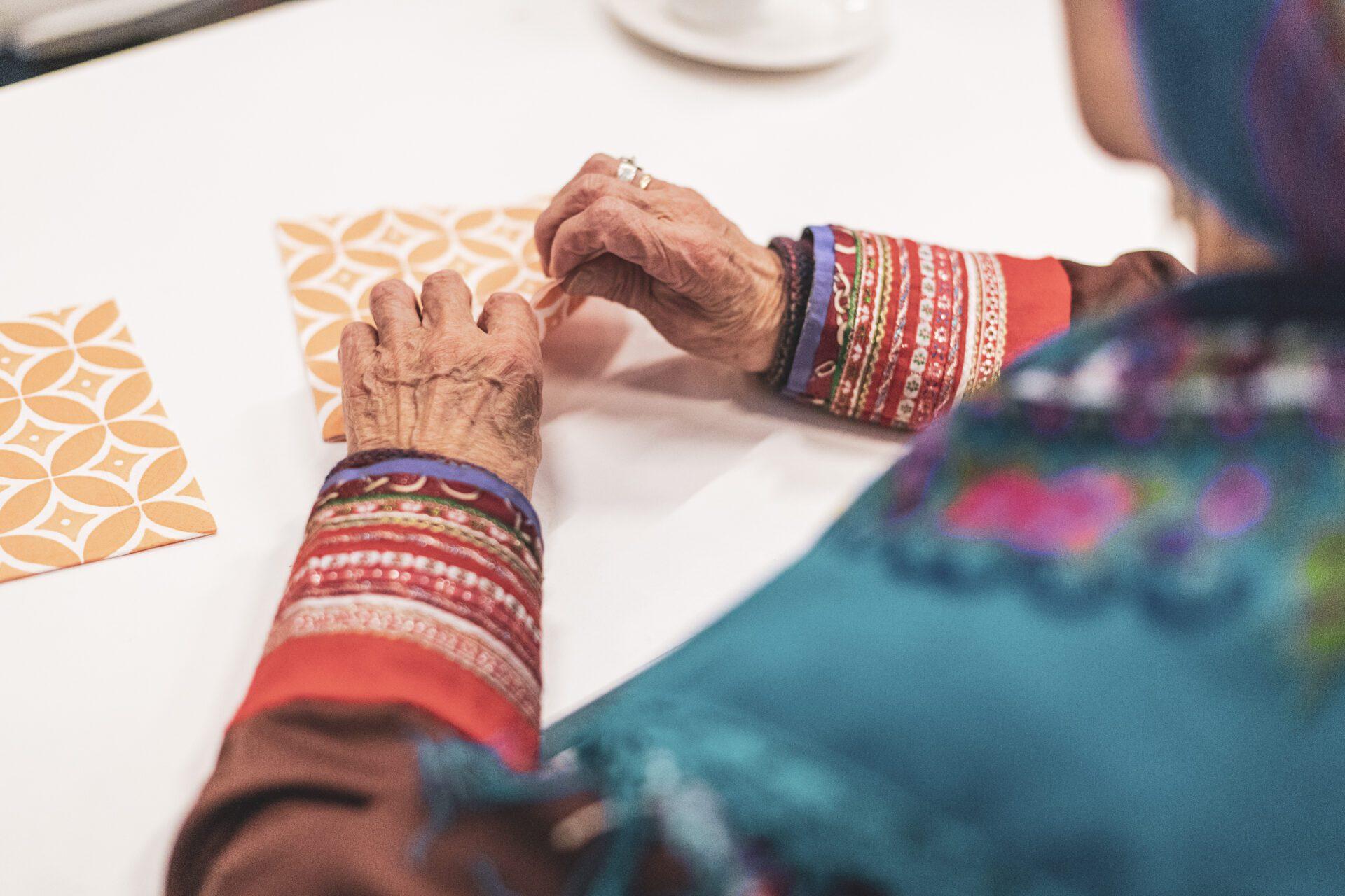 Eldre kvinne i tradisjonelle klær som bretter en serviett