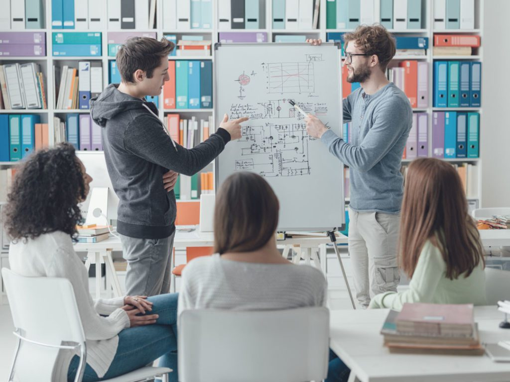 mostphotos.com - desc.: Researcher giving a lecture to the students. Universitetspedagogikk for stipendiater